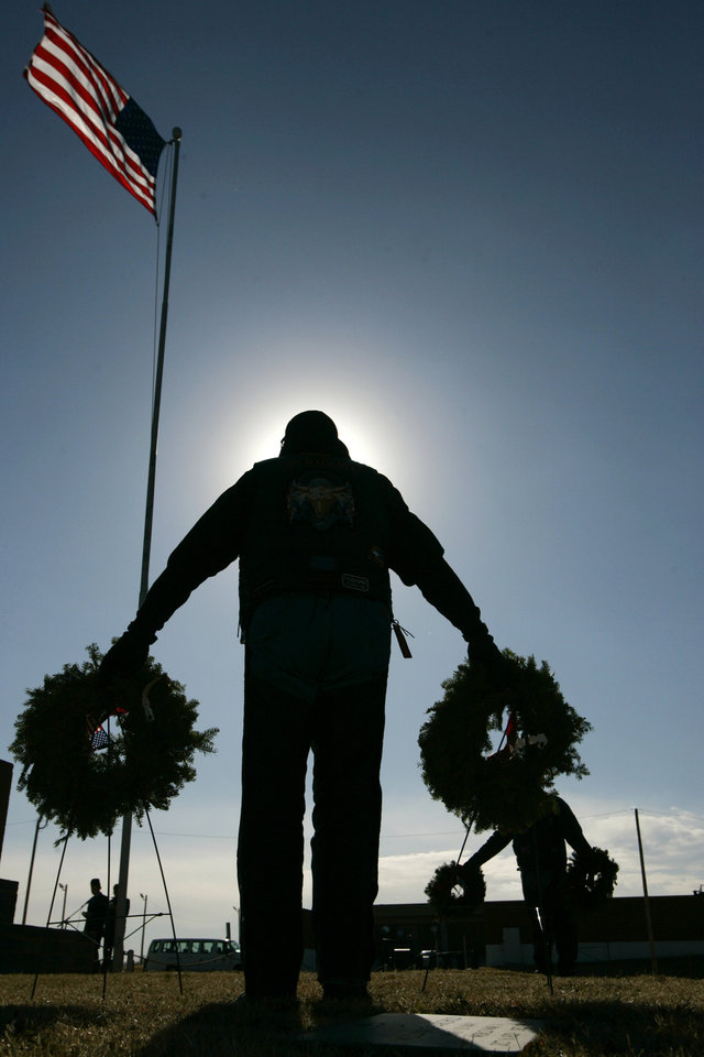 Photo - Mark Johns holds wreaths at Oklahoma Veterans Cemetery during a Wreaths Across America ceremony in Oklahoma City , Okla. December 13, 2008. Johns is a member of the Iron Plainsmen Motorcycle Club,  a brotherhood of law enforcement officers, their spouses, and friends.  BY STEVE GOOCH, THE  OKLAHOMAN.  ORG XMIT: KOD