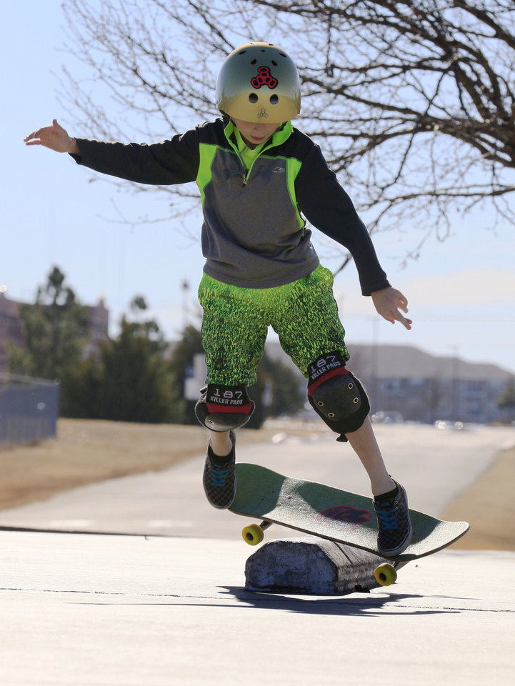 Photo -  T. J. Cooper, 9, practices on his skateboard at the Mathis Brothers Skate Park in Edmond. [PHOTO BY PAUL HELLSTERN, THE OKLAHOMAN]