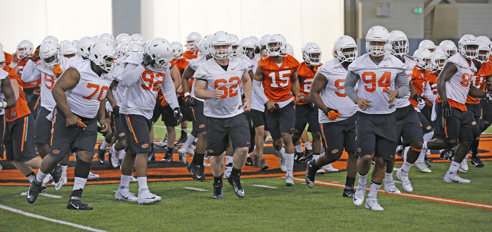 Photo -  The Oklahoma State Cowboys break from a huddle on Monday and get ready to start spring football practice. [PHOTO BY STEVE GOOCH, THE OKLAHOMAN]