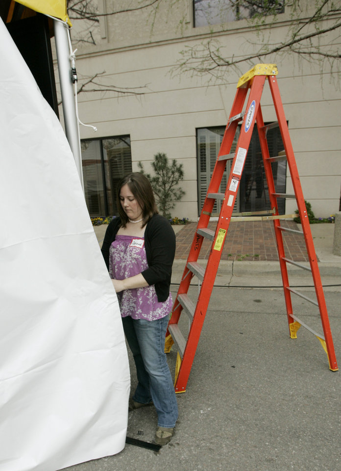 Carrie Coppernoll helps other volunteers set up new tents for the 2009 Festival of the Arts in downtown Oklahoma City, Oklahoma, Thursday, April 16, 2009. Photo by Steve Gooch, The Oklahoman