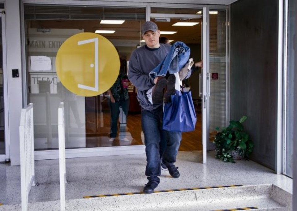 Photo - Warren Rawls, who was released from prison through commutation on Monday, leaves The Education and Employment Ministry (TEEM) office with clothing and other essentials in Oklahoma City, Okla. on Tuesday, Nov. 5, 2019. TEEM and other area nonprofit groups and community partners are working to help people who were released through Monday's commutation make the transition to life outside of prison.      [Chris Landsberger/The Oklahoman]