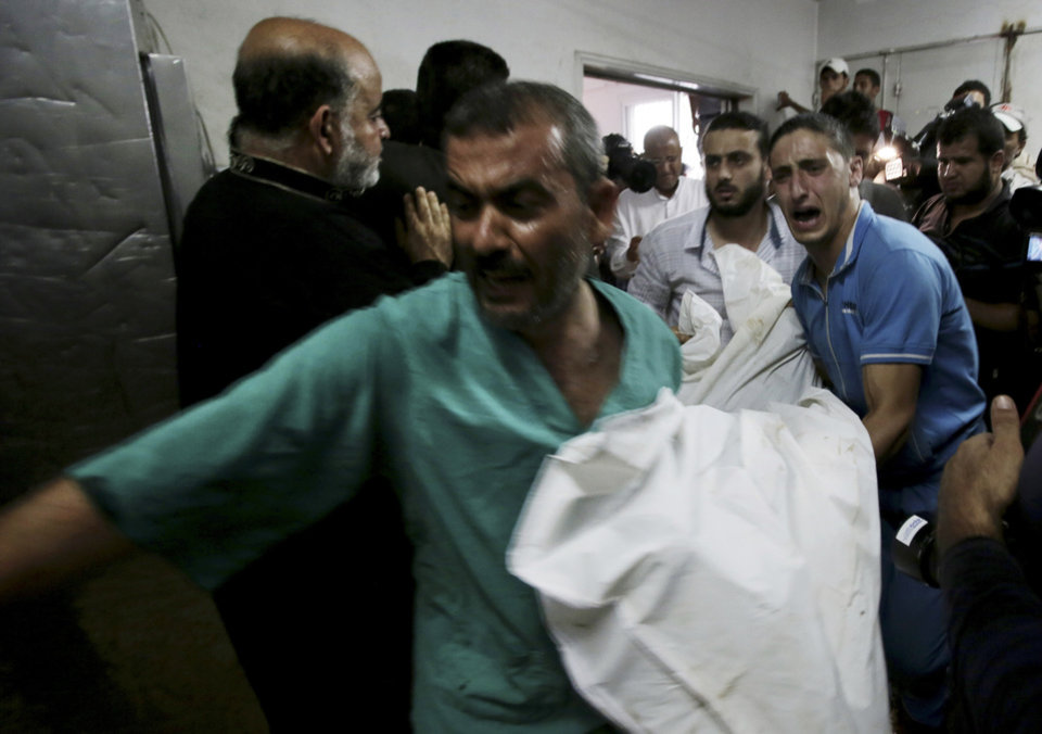 Photo - Palestinians carry a dead body into the morgue of Shifa hospital following an explosion that killed 10 people, all but one of them children, at a park at the Shati refugee camp, in the northern Gaza Strip, Monday, July 28, 2014. Israeli and Palestinian authorities traded blame over the attack and fighting in the Gaza war raged on despite a major Muslim holiday. (AP Photo/Adel Hana)