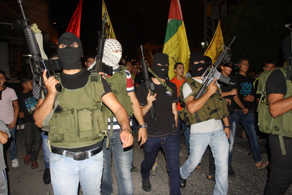 Photo - Masked Palestinian militants of Al-Aqsa Martyrs Brigades, march during a demonstration against the Israeli military action in Gaza, in Balata refugee camp in the West Bank city of Nablus, Saturday, July 26, 2014. Hamas said it fired five rockets at Israel late Saturday after rejecting Israel's offer to extend a 12-hour humanitarian cease-fire by four hours, casting new doubt on international efforts to broker an end to 19 days of fighting. (AP Photo/Nasser Ishtayeh)