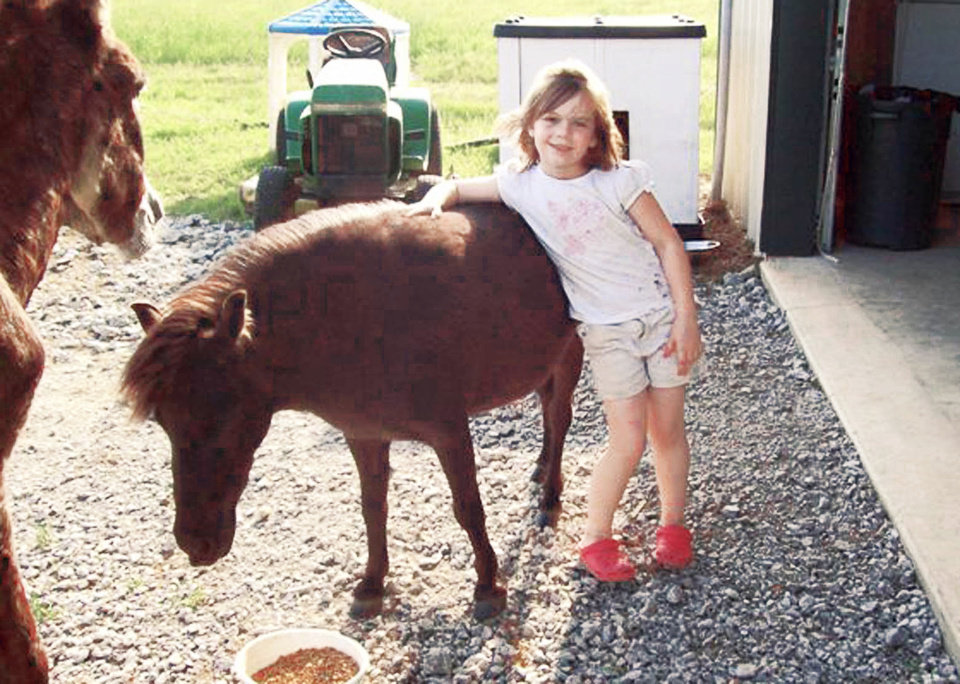 Karma Warren, 6, of Coweta spends some time with her pet miniature horse, Annie. Karma's grandparents recently had to move the pet from their back yard because of city rules. PHOTO PROVIDED