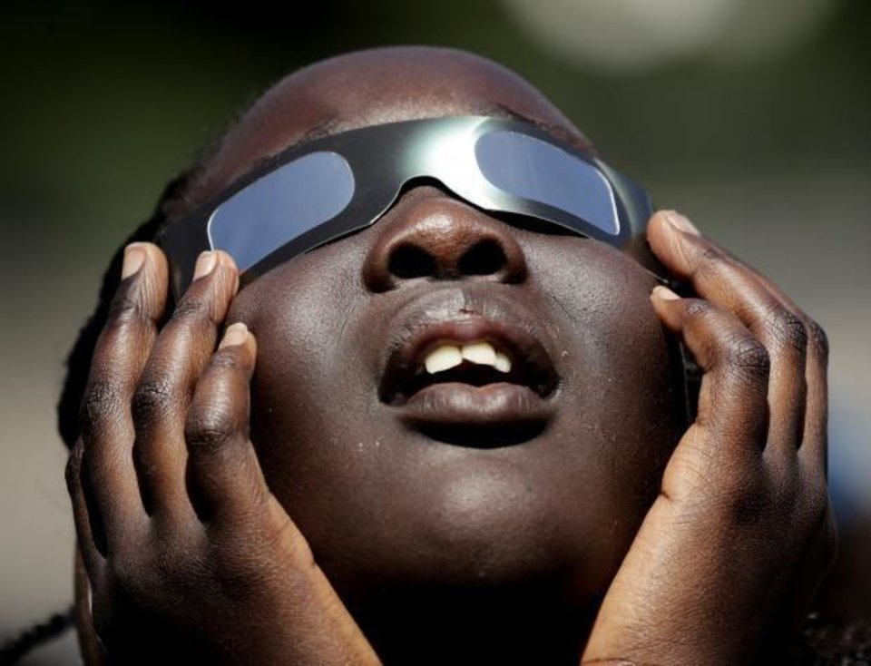 Photo - In this photo taken Friday, Aug. 18, 2017, Poureal Long, a fourth grader at Clardy Elementary School in Kansas City, Mo., practices the proper use of eclipse glasses in anticipation of Monday's solar eclipse. AP photo