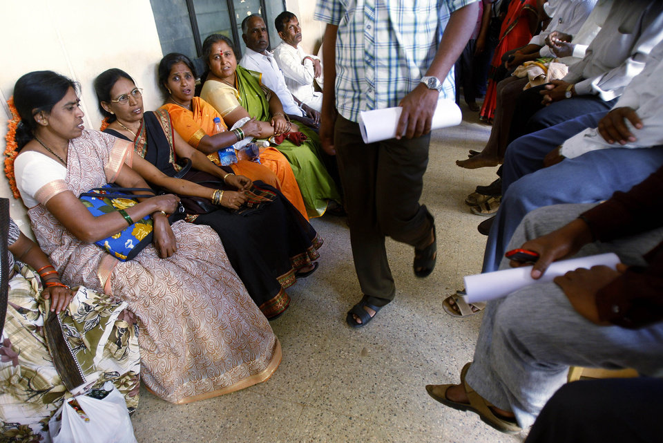 Photo - In this Dec. 10, 2012 photo, people wait to get their land registered at the government registrar's office in Hoskote 30 kilometers (19 miles) from Bangalore, India. For years, Karnataka's land records were a quagmire of disputed, forged documents maintained by thousands of tyrannical bureaucrats who demanded bribes to do their jobs. In 2002, there were hopes that this was about to change. (AP Photo/Aijaz Rahi)