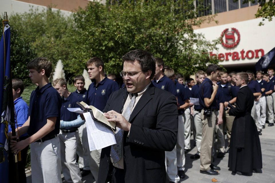 Photo - Patrick Werick, of St. Marys Kansas, leads the singing of hymns during a processional from the Sheraton to the Civic Center Music Hall, Sunday, Sept. 21, 2014.  Photo by Garett Fisbeck, For The Oklahoman