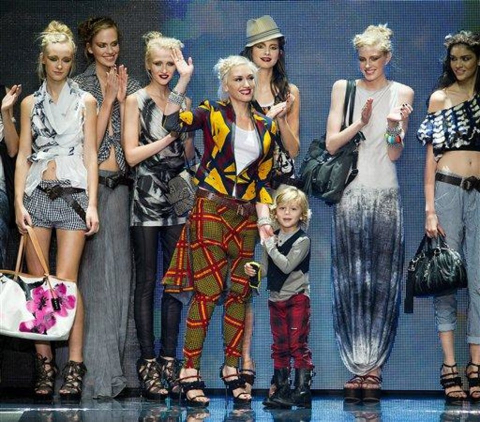 Photo - FILE - In this Sept. 16, 2010 file photo, Gwen Stefani is joined by her son Kingston on the runway after her L.A.M.B. fashion show held during Mercedes-Benz Fashion Week in New York. Stefani is no stranger to multitasking, juggling her music career _ she's wrapping up a new album with No Doubt _ and her fashion projects, which include the debut of the newest Harajuku Mini collection at Target next week.  (AP Photo/Charles Sykes, file)