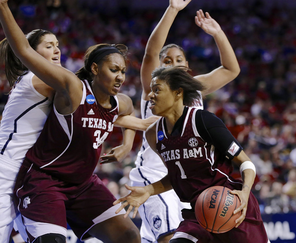 Photo - Texas A&M's Courtney Williams (1) drives to the basket past teammate Karla Gilbert (34), Connecticut's Stefanie Dolson, left, and Connecticut's Kaleena Mosqueda-Lewis, right rear, during the second half of a regional final game in the NCAA college basketball tournament in Lincoln, Neb., Monday, March 31, 2014. (AP Photo/Nati Harnik)