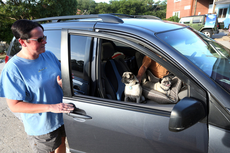 Photo - Susan Holbrook climbs into her car with husband Steve Kozlowski and her two pugs to leave Hatteras Island, N.C., on Wednesday, July 2, 2014.  Moments earlier Dare County had called for a mandatory evacuation because of approaching Tropical Storm Arthur, which is forecast to reach hurricane strength as it nears Hatteras Island.  (AP Photo/The Virginian-Pilot, Steve Earley)  MAGS OUT