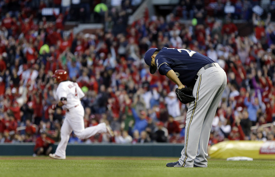 Photo - Milwaukee Brewers starting pitcher Kyle Lohse, right, bends over as St. Louis Cardinals' Yadier Molina rounds the bases after hitting a three-run home run during the first inning of a baseball game Tuesday, April 29, 2014, in St. Louis. (AP Photo/Jeff Roberson)