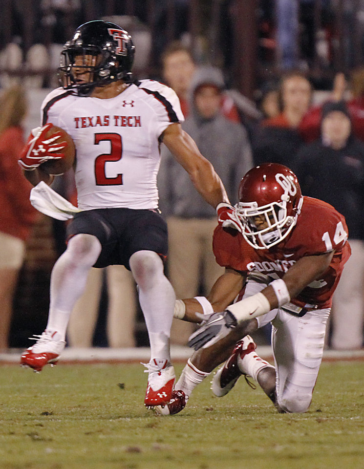 Texas Tech's Cornelius Douglas (2) runs past a tackle attempt by Oklahoma's Aaron Colvin (14) during the college football game between the University of Oklahoma Sooners (OU) and Texas Tech University Red Raiders (TTU) at the Gaylord Family-Oklahoma Memorial Stadium on Saturday, Oct. 22, 2011. in Norman, Okla. Photo by Chris Landsberger, The Oklahoman