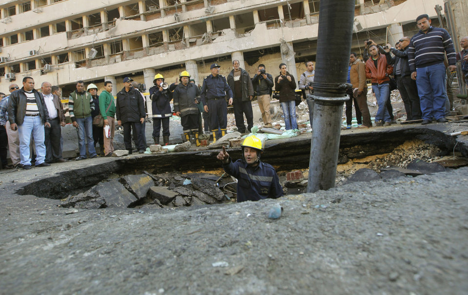 Photo - An Egyptian firefighter checks a crater made by a blast at the Egyptian police headquarters in downtown Cairo, Egypt, Friday, Jan. 24, 2014. Three bombings hit high-profile areas around Cairo on Friday, including a suicide car bomber who struck the city's police headquarters, killing several people in the first major attack on the Egyptian capital as insurgents step up a campaign of violence following the ouster of the Islamist president. (AP Photo/Amr Nabil)