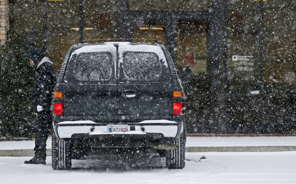 Photo - A man stands outside a vehicle during a winter storm in Oklahoma City, Thursday, December, 5, 2013. Photo by Bryan Terry, The Oklahoman