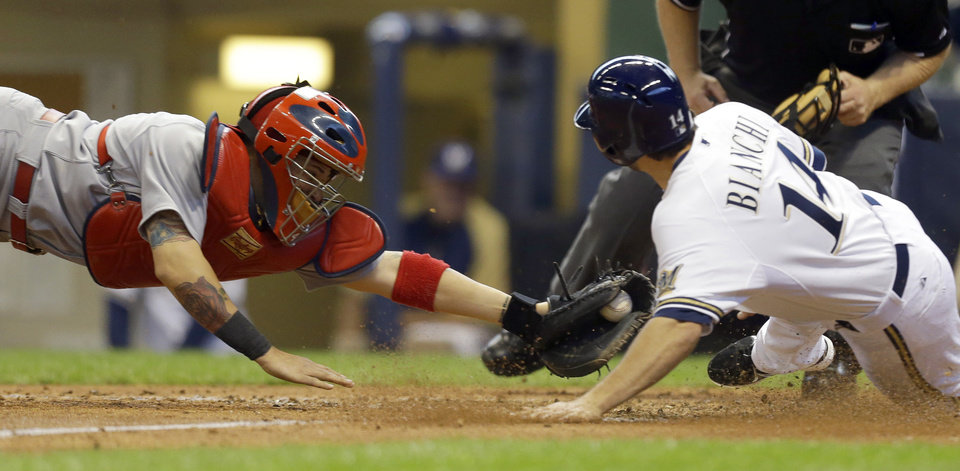 Milwaukee Brewers\' Jeff Bianchi, right, scores ahead of the tag by St. Louis Cardinals\' Yadier Molina during the eight inning of a baseball game Saturday, May 4, 2013, in Milwaukee. (AP Photo/Jeffrey Phelps)