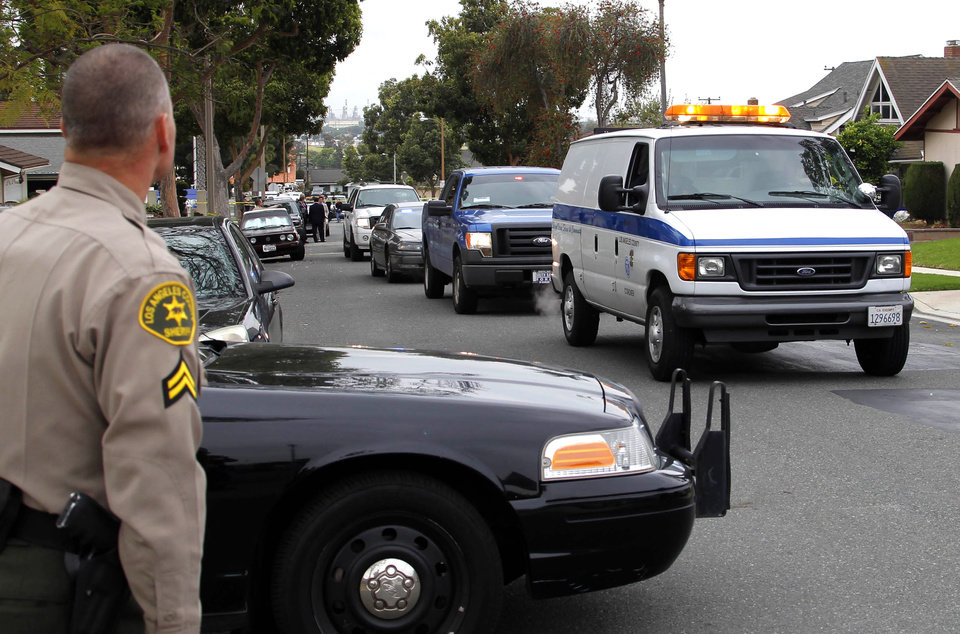 A police officer watches as a coroner's van carrying the body of an ICE agent is followed down the street by a procession of his fellow ICE agents in Carson, Calif. on Thursday. May 3,2012. The 14-year-old son of the federal agent was arrested Thursday in the shooting death of his father in their Southern California home, authorities said. (AP Photo/Nick Ut)