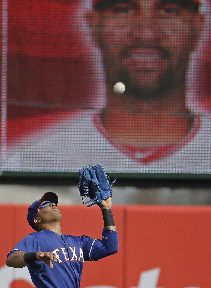 Photo - Texas Rangers' Leonys Martin catches a fly ball hit by Los Angeles Angels' Albert Pujols during the third inning of an exhibition spring training baseball game Tuesday, March 4, 2014, in Tempe, Ariz. (AP Photo/Morry Gash)