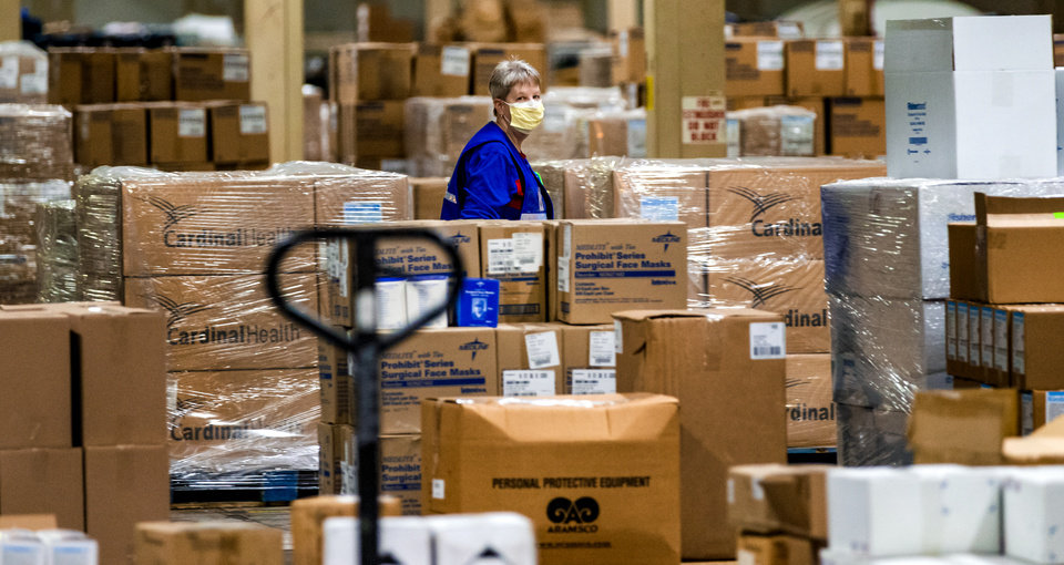 Photo - A worker walks past boxes of personal protection equipment (PPE) and medical supplies at a warehouse where the State of Oklahoma has amassed a stockpile for its COVID-19 response in Oklahoma City, Okla. on Tuesday, April 7, 2020, in a   [Chris Landsberger/The Oklahoman]