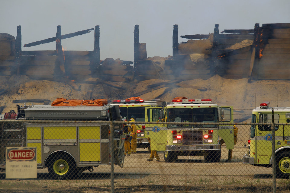 Photo - Fire trucks keep an eye on a burned structure at the Naval Base Ventura County (NBVC) at Point Mugu, Calif., Friday, May 3, 2013. The 15 1/2-square-mile blaze was only 10 percent contained on Friday, and the work of more than 900 firefighters, aided by air tankers, was just beginning. (AP Photo/Nick Ut)