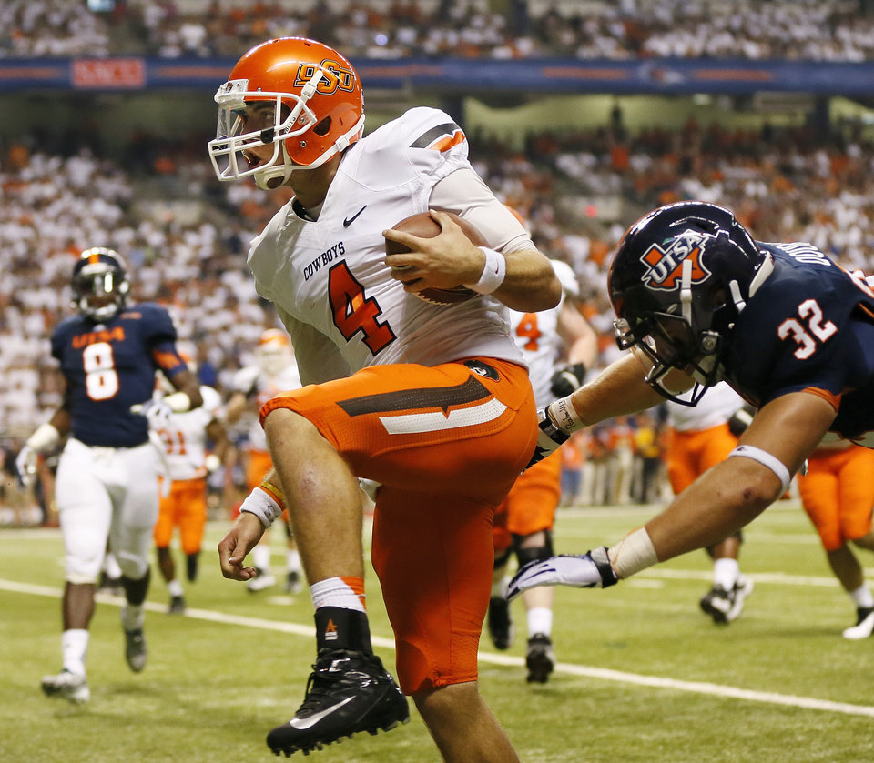 OSU quarterback J.W. Walsh (4) runs through the end zone past UTSA's Drew Douglas (32) as Walsh rushes for a touchdown in the second quarter during a college football game between the University of Texas at San Antonio Roadrunners (UTSA) and the Oklahoma State University Cowboys (OSU) at the Alamodome in San Antonio, Saturday, Sept. 7, 2013.  Photo by Nate Billings, The Oklahoman