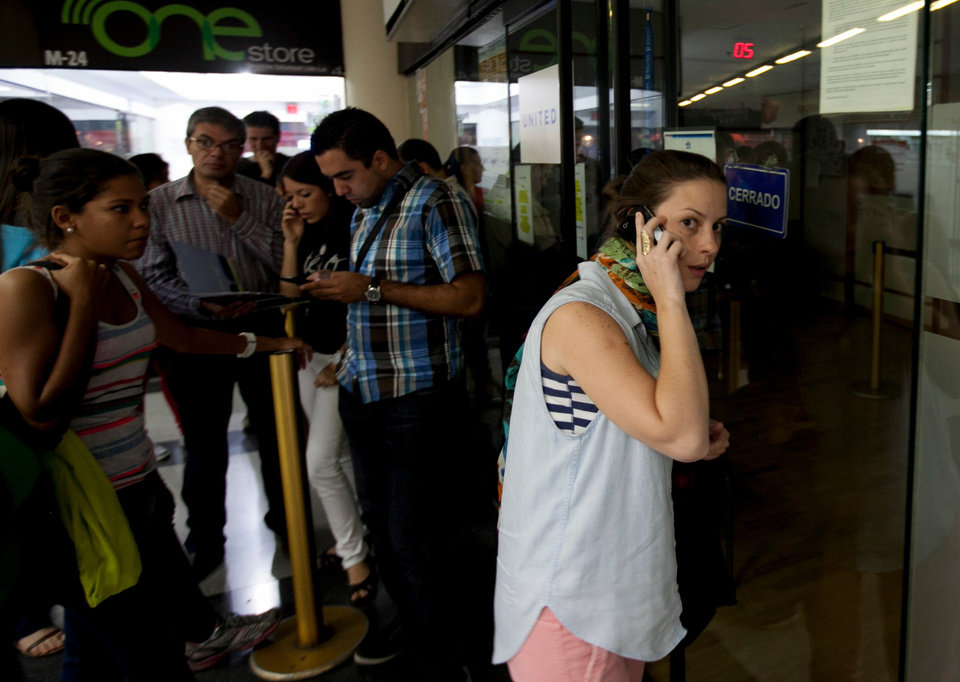 Photo - A woman speaks on her cell as she seeks information about flight sales from a closed United Airlines office in Caracas, Venezuela, Friday, Jan. 24, 2014.  Delta, American Airlines and Panama's Copa Airlines were also among carriers whose offices were either closed or had halted sales on Friday after the government devalued the local currency for flights abroad. (AP Photo/Alejandro Cegarra)