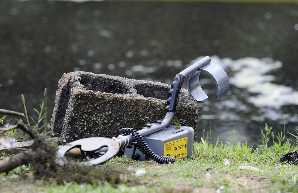 Photo - A metal detector is seen in an area where Connecticut State Police Dive Team are searching on Pine Lake in Bristol, Conn., the hometown of the former New England Patriots player Aaron Hernandez,  Monday, July 29, 2013. Hernandez has pleaded not guilty to murder in the death of Odin Lloyd, a 27-year-old Boston semi-professional football player. (AP Photo/Jessica Hill)