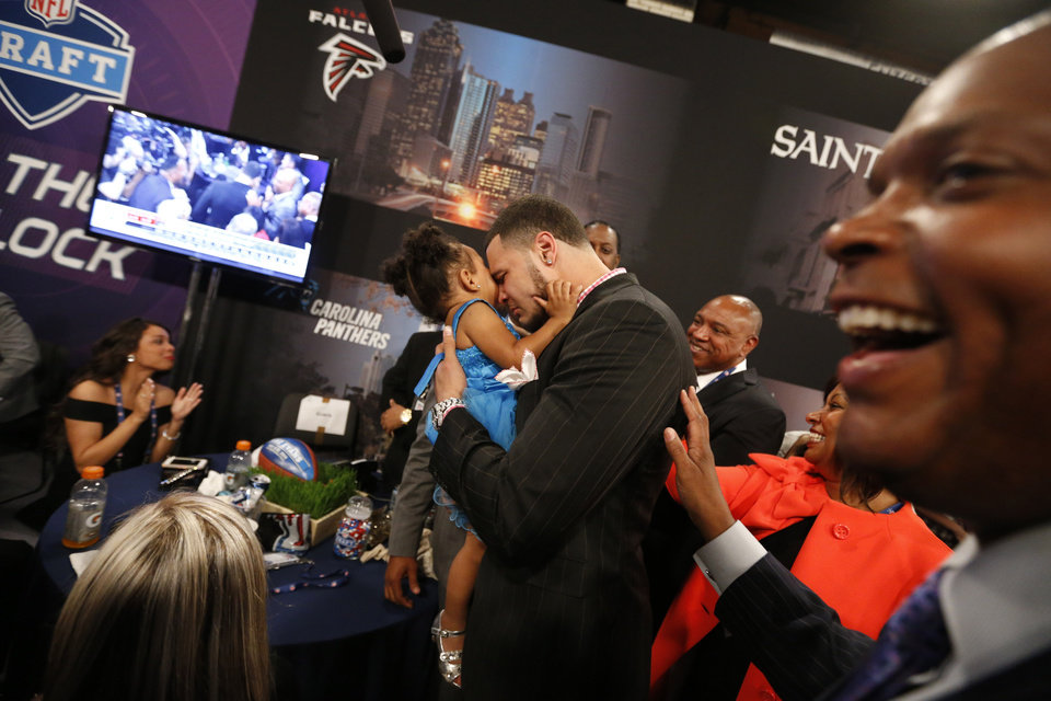 Photo - Mike Evans, from Texas A&M, holds his 2-year-old daughter Mackenzie as he reacts after being selected seventh overall by the Tampa Bay Buccaneers in the first round of the NFL football draft, Thursday, May 8, 2014, at Radio City Music Hall in New York. (AP Photo/Jason DeCrow)