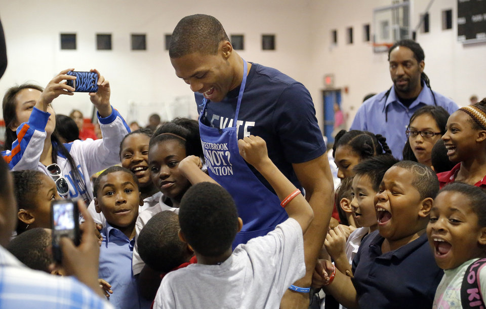 Photo - OKLAHOMA CITY THUNDER NBA BASKETBALL PLAYER / CHARITY / CHILD / KIDS: Oklahoma City's Russell Westbrook greets children during a Thanksgiving dinner at the Boys & Girls Club of Oklahoma County in Oklahoma CIty,  Tuesday, Nov. 20, 2012. Photo by Sarah Phipps, The Oklahoman