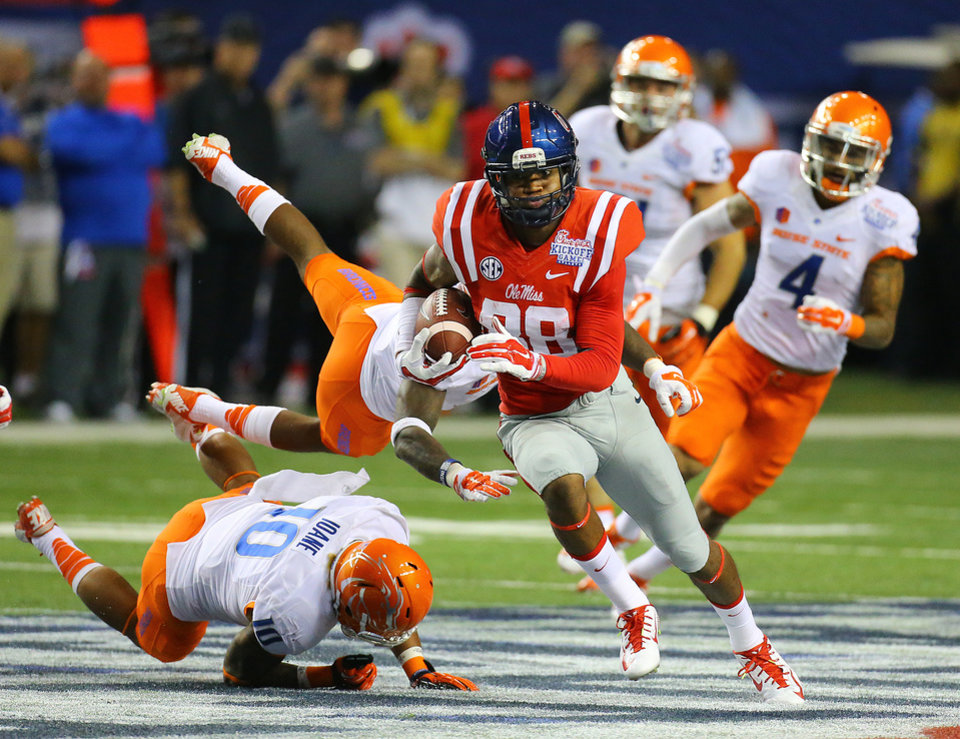 Photo - Mississippi wide receiver Cody Core cuts through Boise State defenders for a 76-yard touchdown during the fourth quarter of an NCAA college football game, Thursday, Aug. 28, 2014 in Atlanta. (AP Photo/Atlanta Journal-Constitution, Curtis Compton)  MARIETTA DAILY OUT; GWINNETT DAILY POST OUT; LOCAL TELEVISION OUT; WXIA-TV OUT; WGCL-TV OUT