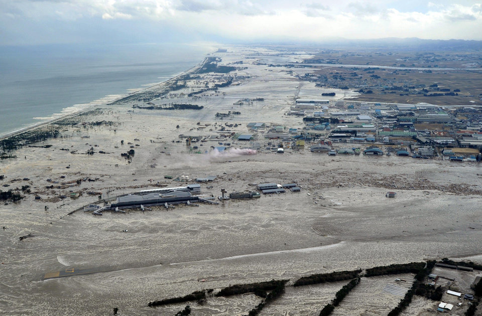 Photo - Earthquake-triggered tsunami sweeps the shore as Sendai Airport is surrounded by waters in Miyagi prefecture (state), Japan, Friday, March 11, 2011. The ferocious tsunami spawned by one of the largest earthquakes ever recorded slammed Japan's eastern coasts. (AP Photo/Kyodo News) JAPAN OUT, MANDATORY CREDIT, FOR COMMERCIAL USE ONLY IN NORTH AMERICA ORG XMIT: TTX816