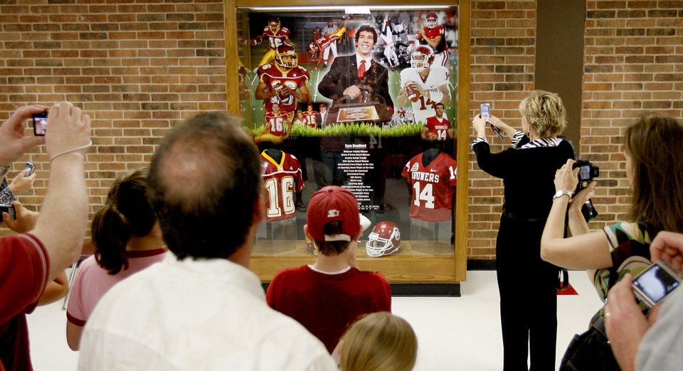 Photo - JERSEY RETIREMENT: A crowd gathers around a trophy case honoring University of Oklahoma (OU) college football quarterback Sam Bradford after a ceremony to honor Bradford and retire his jersey at Putnam City North High School in Oklahoma City, Friday, April 24, 2009. Photo by Bryan Terry, The Oklahoman ORG XMIT: KOD
