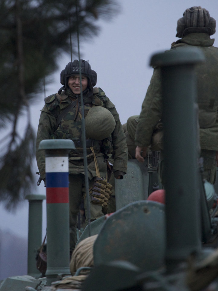 Photo - A soldier smiles as he stands atop a Russian armored personnel carrier near the town of Bakhchisarai, Ukraine, Friday, Feb. 28, 2014. The vehicles were parked on the side of the road near the town of Bakhchisarai, apparently because one of them had mechanical problems. (AP Photo/Ivan Sekretarev)