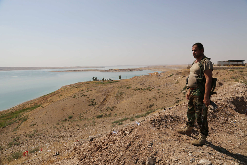 Photo - A Kurdish peshmerga fighter stands guard near the Mosul Dam at the town of Chamibarakat outside Mosul, Iraq, Sunday, Aug. 17, 2014. Kurdish forces took over parts of the largest dam in Iraq on Sunday less than two weeks after it was captured by the Islamic State extremist group, Kurdish security officials said, as U.S. and Iraqi planes aided their advance by bombing militant targets near the facility. (AP Photo/Khalid Mohammed)