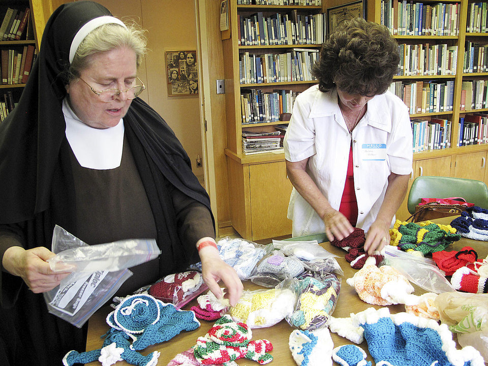 Photo - Sister Marcianne Kappes and Barbara Hallauer of Moore look at doll clothes in the library area of Villa Teresa Convent during the Carmelite Sisters of St. Therese's 95th anniversary and alumni gathering on June 8 at Villa Teresa Convent and School in Oklahoma City. Kappes and several of her friends created the clothes and Hallauer purchased some of them with the proceeds to go to a homeless ministry in Shawnee. Photo by Carla Hinton, The Oklahoman