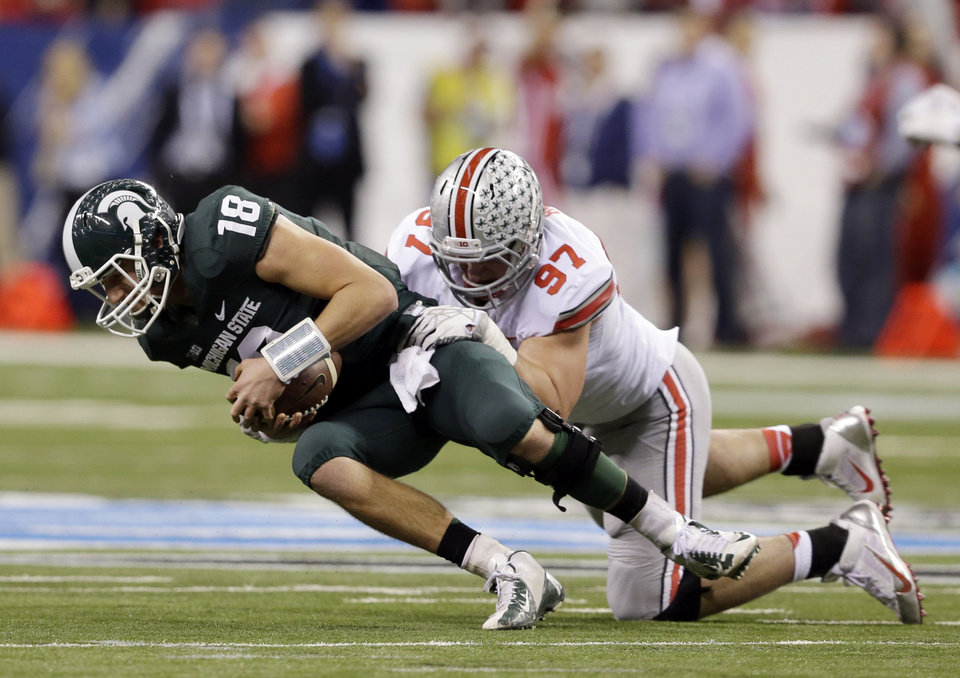 Photo - FILE - In this Dec. 7, 2013, file photo, Michigan State's Connor Cook (18) is sacked by Ohio State's Joey Bosa (97) during the first half of a Big Ten Conference championship NCAA college football game in Indianapolis. For Saturday's, Aug. 30, 2014, season opening game with Navy, Bosa and the Ohio State defense must get ready for the Midshipmen's lethal triple-option game. (AP Photo/Darron Cummings, File)