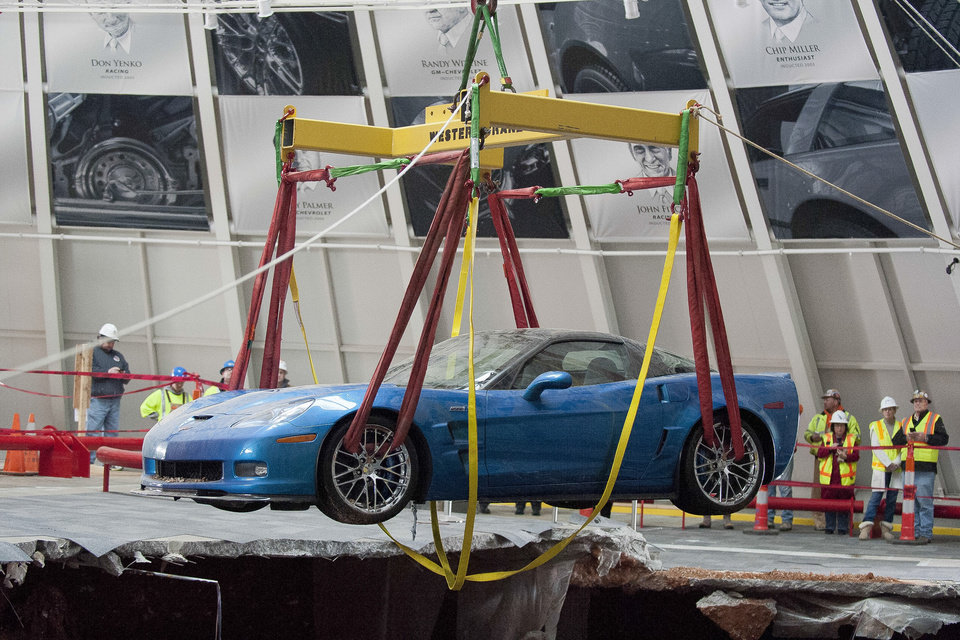 Photo - One of eight Chevrolet Corvettes is removed from a sinkhole in the Skydome at the National Corvette Museum, Monday, March. 3, 2014, in Bowling Green, Ky.  On Feb. 12, a large sinkhole swallowed eight prized cars like they were toys, piling them in a heap amid loose dirt and concrete fragments. (AP Photo/Daily News, Alex Slitz)