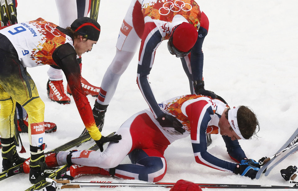 Photo - Norway's gold medal winner Joergen Graabak, right, is congratulated by Germany's bronze medal winner Fabian Riessle, left, and Norway's Magnus Hovdal Moan, top right, after the cross-country portion of the Nordic combined individual Gundersen large hill competition at the 2014 Winter Olympics, Tuesday, Feb. 18, 2014, in Krasnaya Polyana, Russia. (AP Photo/Dmitry Lovetsky)