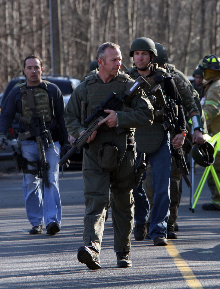 Photo - Heavily armed Connecticut State troopers are on the scene at Sandy Hook Elementary School in Newtown, Conn. where authorities say a gunman opened fire, leaving 27 people dead, including 20 children, Friday, Dec. 14, 2012.(AP Photo/The Journal News, Frank Becerra Jr.) MANDATORY CREDIT, NYC OUT, NO SALES, TV OUT, NEWSDAY OUT; MAGS OUT ORG XMIT: NYWHI110