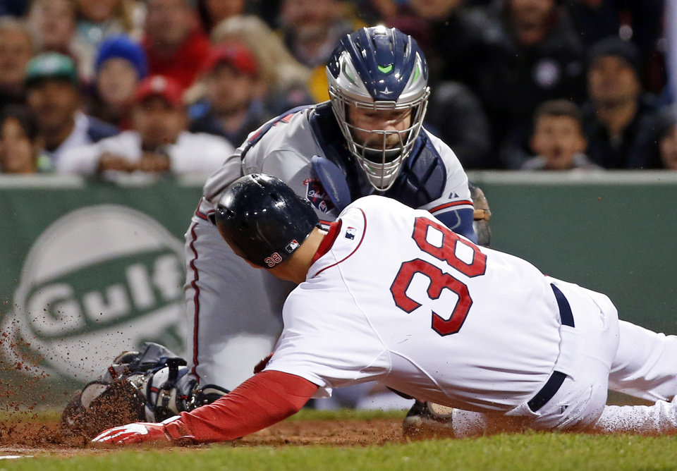 Photo - Atlanta Braves catcher Evan Gattis puts the tag on Boston Red Sox's Grady Sizemore (38) who is out trying to score on a fielder's choice in the sixth inning of a baseball game at Fenway Park in Boston, Wednesday, May 28, 2014. (AP Photo/Elise Amendola)