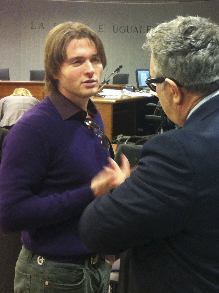 Photo - Raffaele Sollecito talks with an unidentified man prior to the start of the final hearing before the third court verdict for the murder of British student Meredith Kercher, in Florence, Italy, Thursday, Jan. 30, 2014. The first two trials produced flip-flop verdicts of guilty then innocent for Kercher former roommate, American student Amanda Knox, who is not attending the hearing,  and her former Italian boyfriend, Raffaele Sollecito, and the case has produced harshly clashing versions of events. A Florence appeals panel designated by Italy's supreme court to address issues it raised about the acquittal is set to deliberate Thursday, with a verdict expected later in the day. (AP Photo/Fabrizio Giovannozzi)