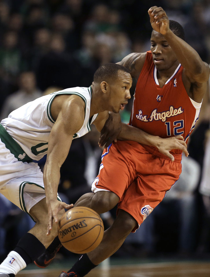 Photo - Boston Celtics guard Avery Bradley (0), left, tries to drive past Los Angeles Clippers guard Eric Bledsoe (12), right, in the first quarter of an NBA basketball game at the TD Garden in Boston, Sunday, Feb. 3, 2013. (AP Photo/Steven Senne)