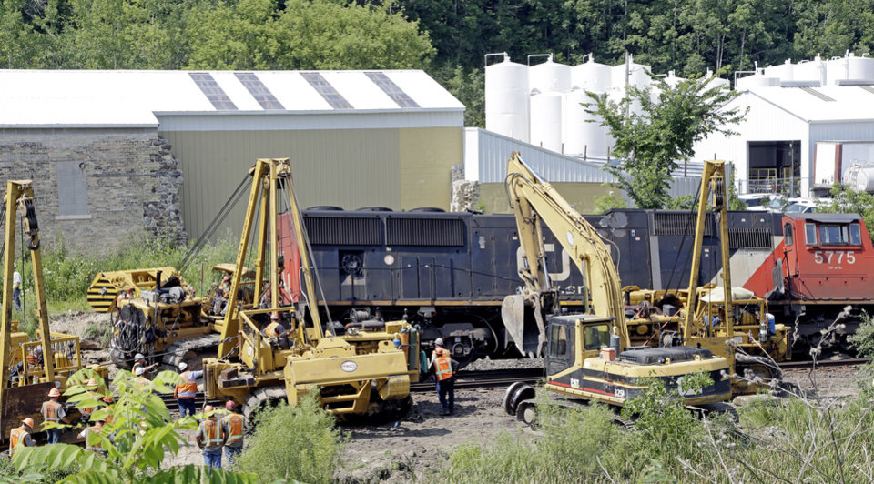Photo - Workers clean up a train derailment Monday, July 21, 2014, in Slinger, Wis. A southbound Canadian National train struck several Wisconsin & Southern Railroad cars around 8:30 p.m. Sunday at a rail crossing in Slinger, Wis., according to Patrick Waldron, a Canadian National spokesman. The derailment injured at least two people and spilled thousands of gallons of fuel that prompted the evacuation of dozens of homes, but evacuees were allowed to return around 1:30 a.m. Monday, Slinger Fire Chief Rick Hanke said. (AP Photo/Morry Gash)