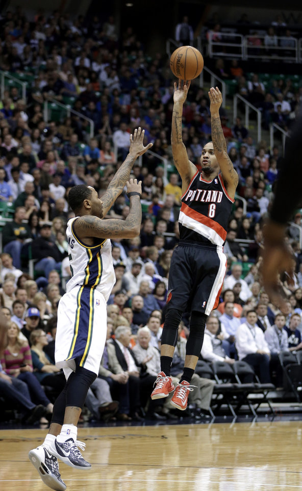 Photo - Portland Trail Blazers' Eric Maynor (6) shoots as Utah Jazz's Mo Williams, left, defends in the first quarter during an NBA basketball game Monday, April 1, 2013, in Salt Lake City.  (AP Photo/Rick Bowmer)