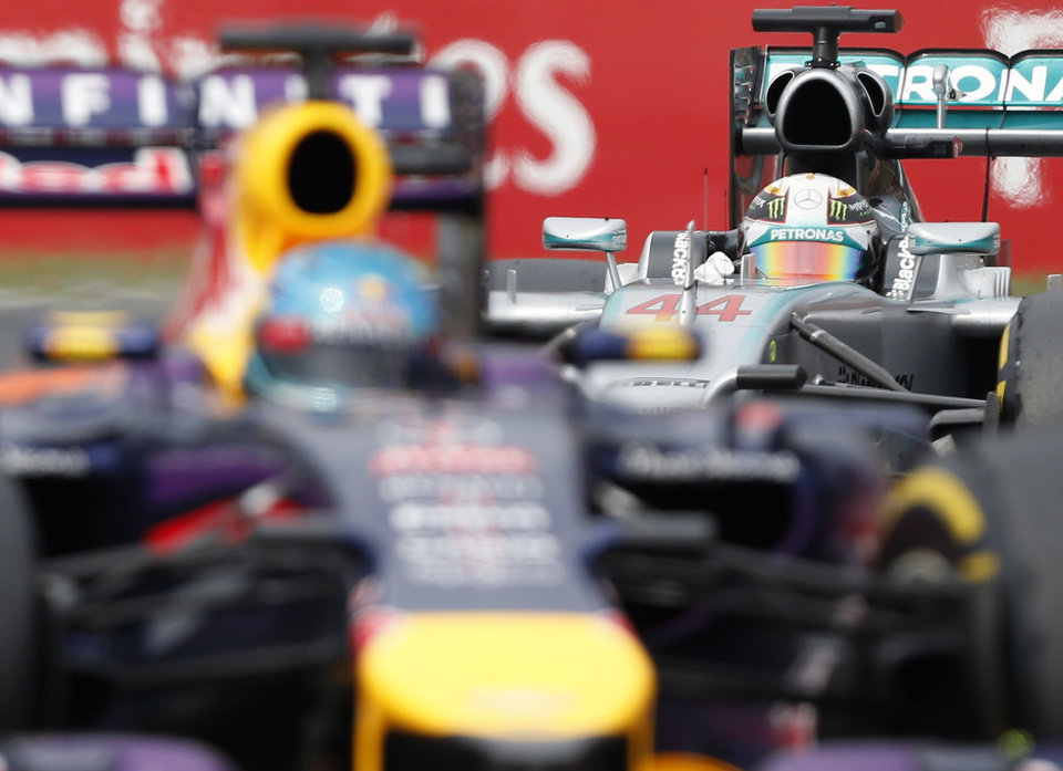 Photo - Mercedes driver Lewis Hamilton, right, of Britain steers his car following Red Bull driver Sebastian Vettel, left, of Germany during the Hungarian Formula One Grand Prix in Budapest, Hungary, Sunday, July 27, 2014. Hamilton placed third in the race. (AP Photo/Darko Vojinovic)