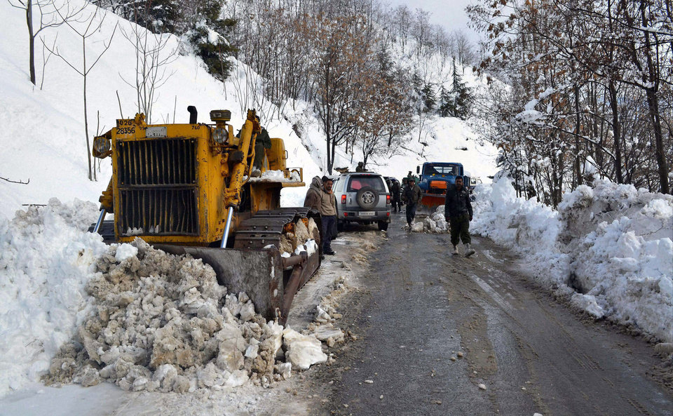 A snow plow machine works to clear the highway in Banihal, India, Saturday, Jan. 19, 2013. Traffic on the 300 kilometers (186 miles) long Jammu-Srinagar national highway was suspended due to heavy snowfall, according to news reports. (AP Photo)