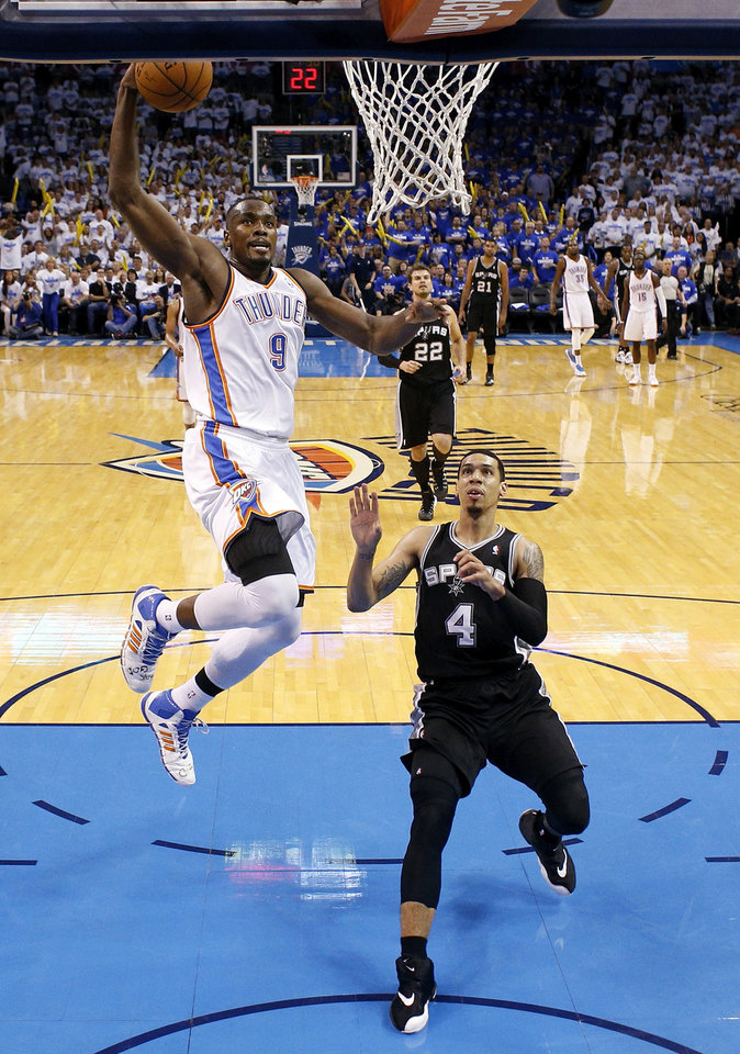 Photo - Oklahoma City's Serge Ibaka (9) dunks the ball in front of San Antonio's Danny Green (4) during Game 4 of the Western Conference Finals in the NBA playoffs between the Oklahoma City Thunder and the San Antonio Spurs at Chesapeake Energy Arena in Oklahoma City, Tuesday, May 27, 2014. Oklahoma City won 105-92. Photo by Nate Billings, The Oklahoman