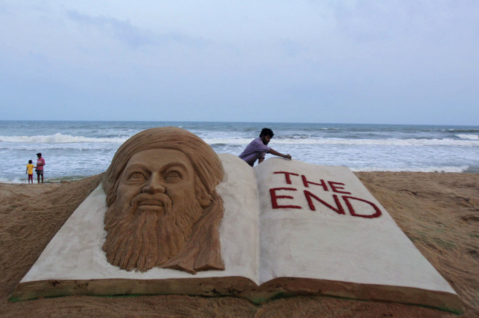 Photo - Indian sand artist Sudarshan Pattnaik gives finishing touches to a sand sculpture to mark the killing of Osama bin Laden at the golden sea beach at Puri, Orissa, India, Monday, May 2, 2011. Osama bin Laden, the mastermind behind the Sept. 11, 2001, terror attacks that killed thousands of people, was slain in his luxury hideout in Pakistan early Monday in a firefight with U.S. forces, ending a manhunt that spanned a frustrating decade.(AP Photo/Biswaranjan Rout) ORG XMIT: DEL134
