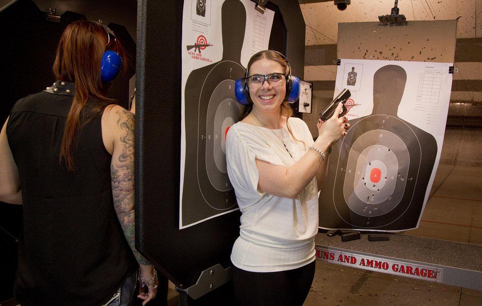 Photo - Tanya Morris, right, poses for a photo with her shot-up target after getting married at the Guns and Ammo Garage, Thursday, Feb. 14, 2013, in Las Vegas. Las Vegas is embracing tourists' newfound interest in big guns the only way it knows how: by going all in. The shooting range and gun store offered free vow renewals and wedding ceremonies  throughout the day on Thursday. (AP Photo/Julie Jacobson)