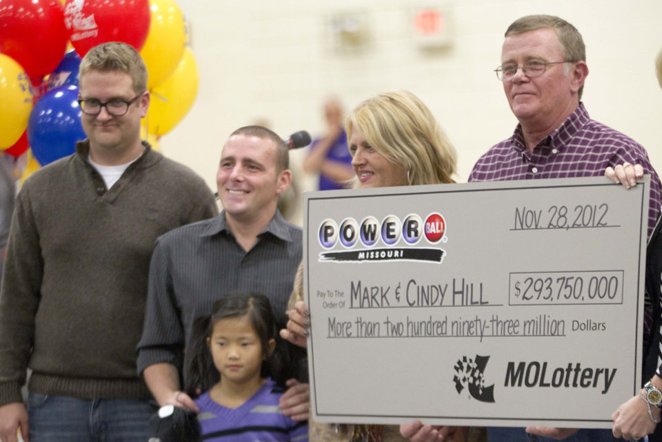 Mark and Cindy Hill hold a Powerball check with their three of their four children,  Jarod, left, Cody and six-year-old Jaiden in Dearborn, Mo., Friday, Nov. 30, 2012. (AP Photo/Orlin Wagner)