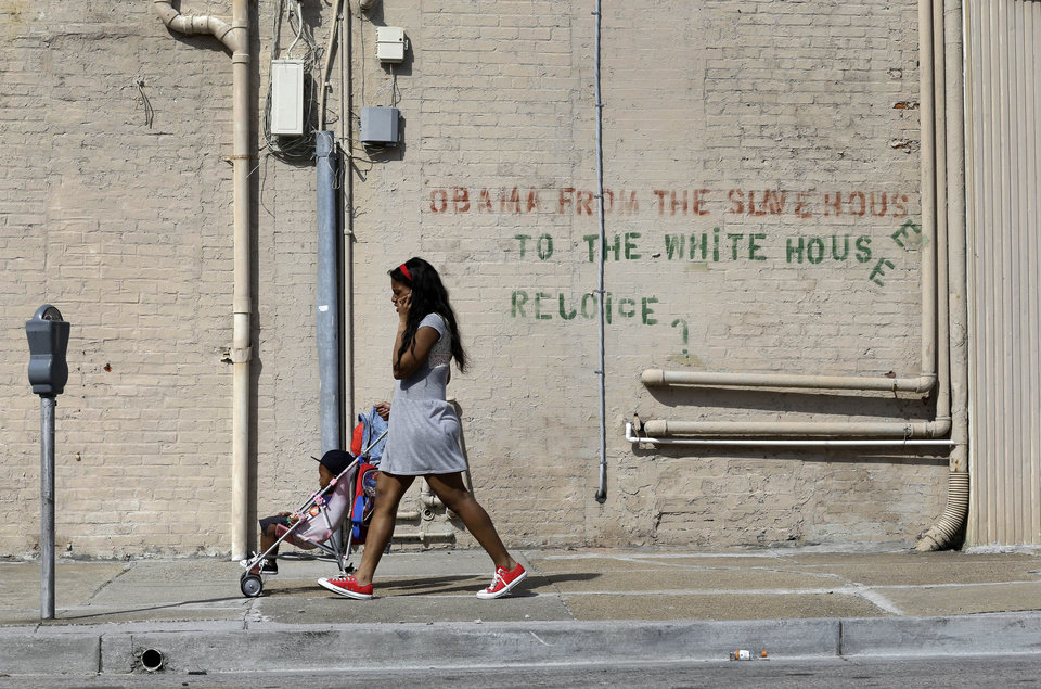 Photo - In this April 9, 2013 picture, a woman pushes a boy in a stroller past graffiti on a wall in Baltimore. The U.S. Census Bureau estimates that 20 percent of American children are impoverished. (AP Photo/Patrick Semansky)